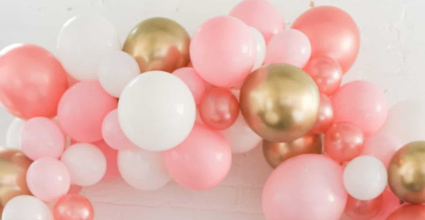 An assortment of pink, white, and gold balloons